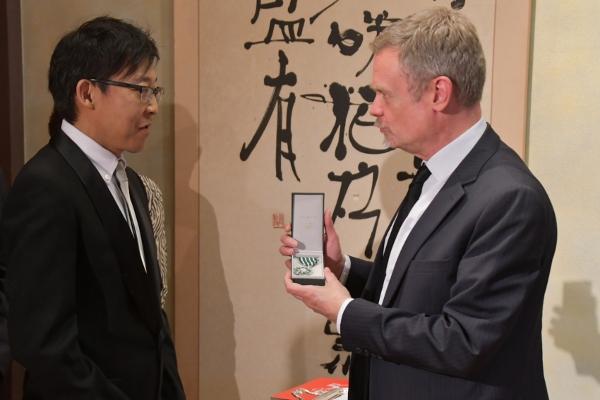 M. Akio Iyoku, éditeur de M. Akira Toriyama, reçoit les insignes de Chevalier dans l'Ordre des Arts et des Lettres des mains de M. l'ambassadeur, Laurent Pic.